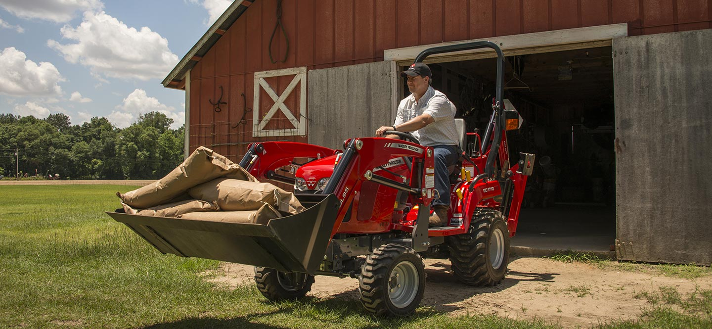 Massey Ferguson Utility Tractor moving large bags with front-end loader