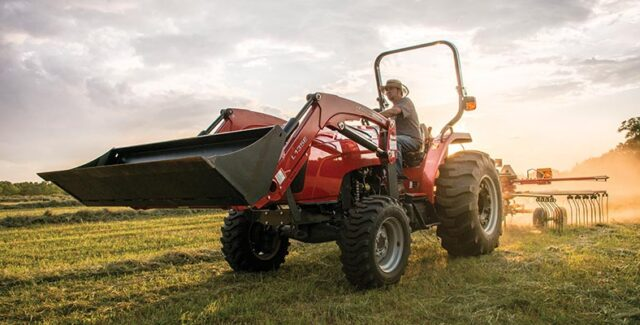 Man on Massey-Ferguson tractor with front-end loader